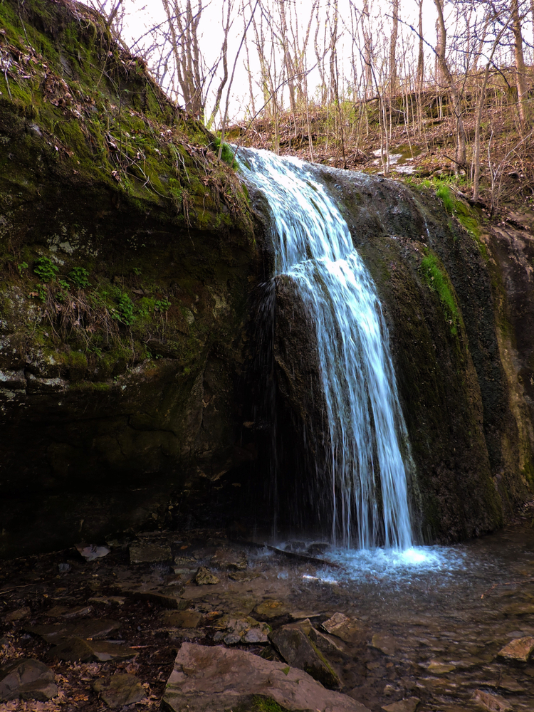 The small Stephens Falls waterfall flowing over a large round boulder in the late fall or early spring on a cloudy day
