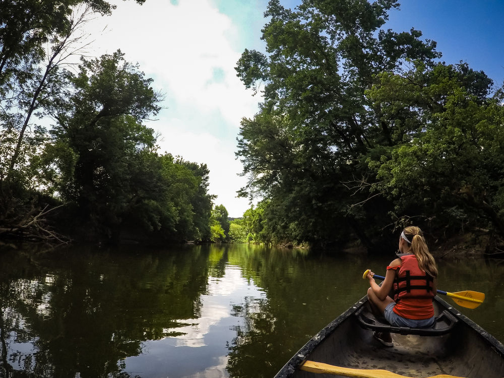 Young blonde woman sitting in canoe holding paddle riding calm water with trees on either side of river.