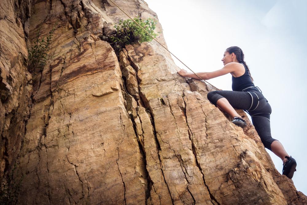Caucasian woman wearing black, rock climbing up brown rocks.
