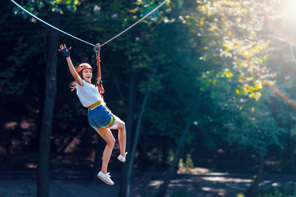 Caucasian girl zip lining, waving and smiling. A really fun thing to do in Hocking Hills.