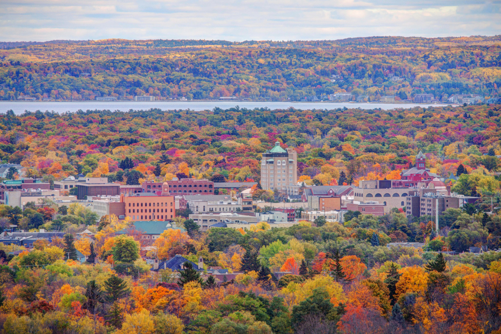An aerial image of Traverse City Michigan in the fall surrounded by trees changing color