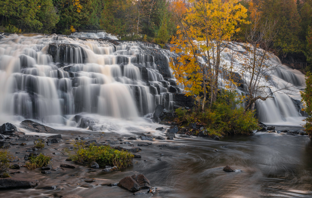 The incredible Bond Waterfalls in Michigan. Its a rock step fall and there is a tree in the foreground.