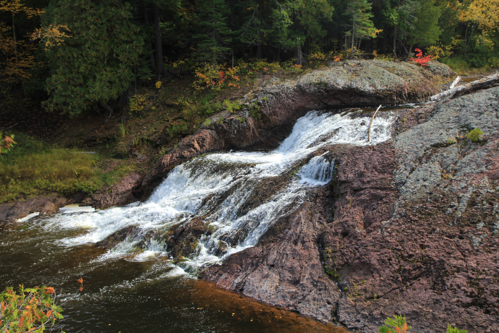 Water tumbling over a large rock with a forest in the background Great Conglomerate is one of the waterfalls in Michigan