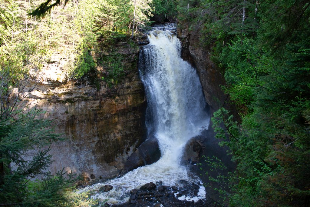 Munising waterfalls in Michigan . It's a large fall tumbling off a cliff with foliage around the cliff.
