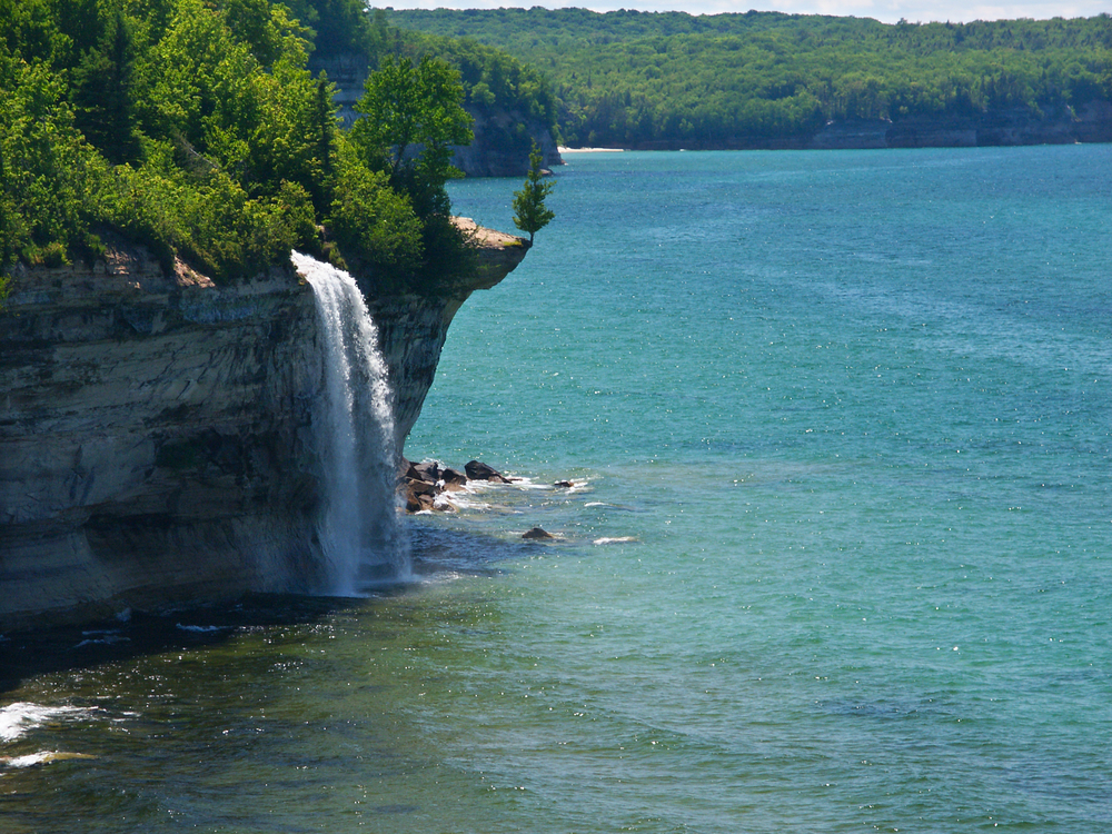 A waterfall tumbling from a tree lined cliff into a large lake below.