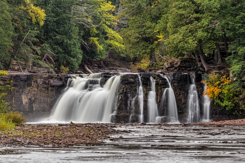 Water cascading down a rock cliff with foliage in the background on the beautiful Manabezho River, one of the waterfalls in Michigan