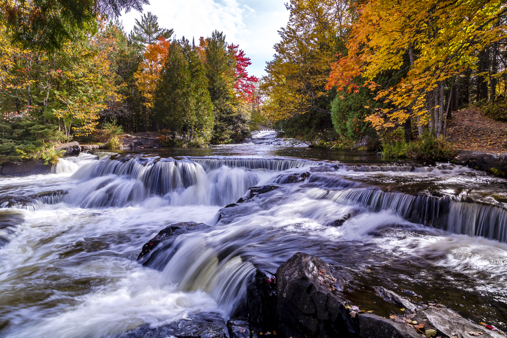 Water tumbling on rocks with a waterfall and fall foilage in the background in an article about waterfalls in Michigan
