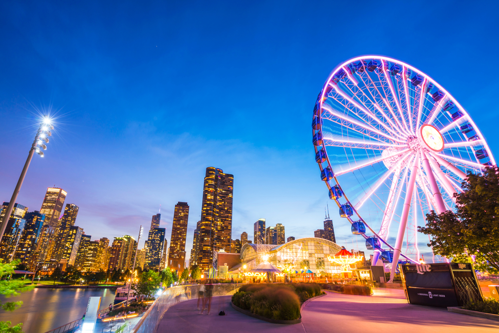 Gleaming Ferris Wheel and city skyscrapers with lights turned on at sunset. 2 days in Chicago itinerary destination.