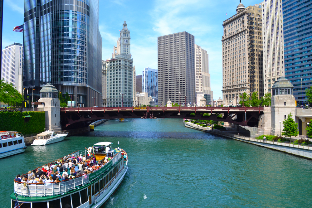 Large boat sailing the Chicago River with tourists on top observation deck.