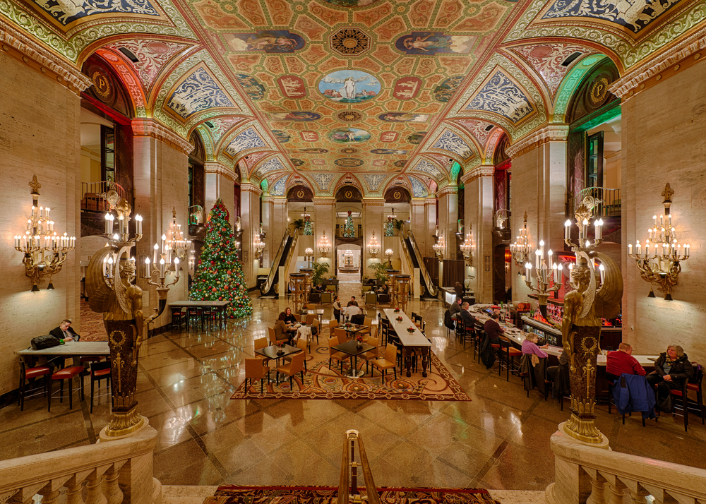 Opulent hotel lobby with chandeliers on walls, fancy colorful ceiling and decorated Christmas tree on left.