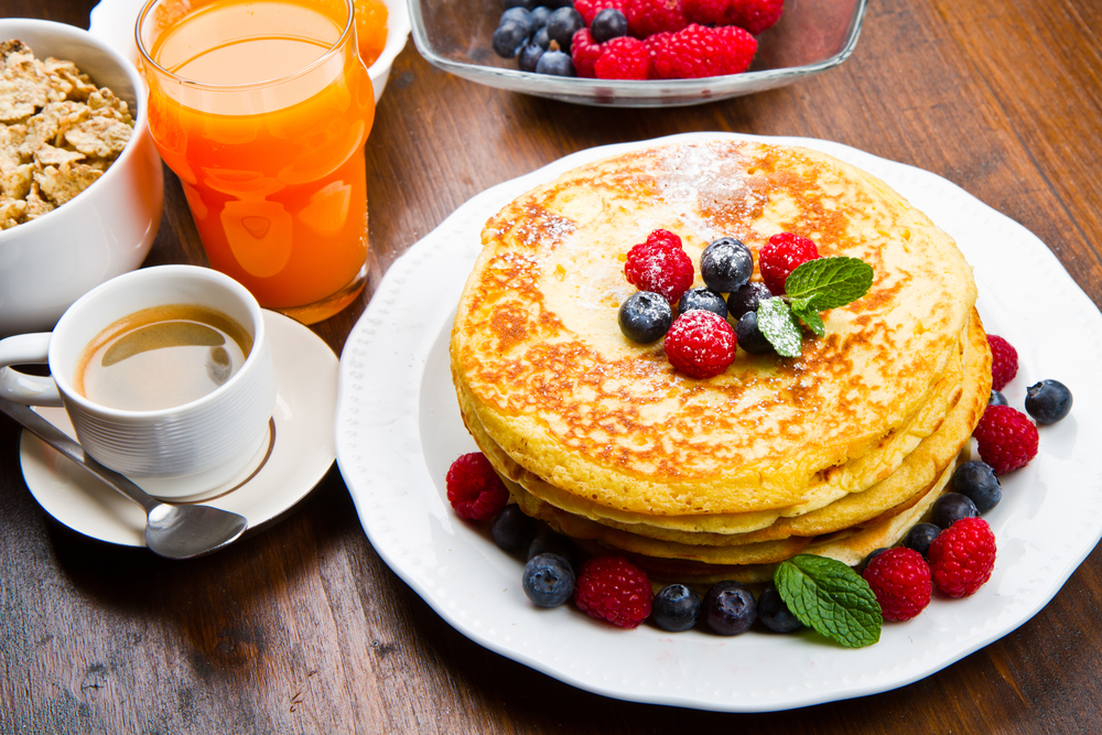 Pancakes and berries alongside a cup of coffee in an article about breakfast in Chicago