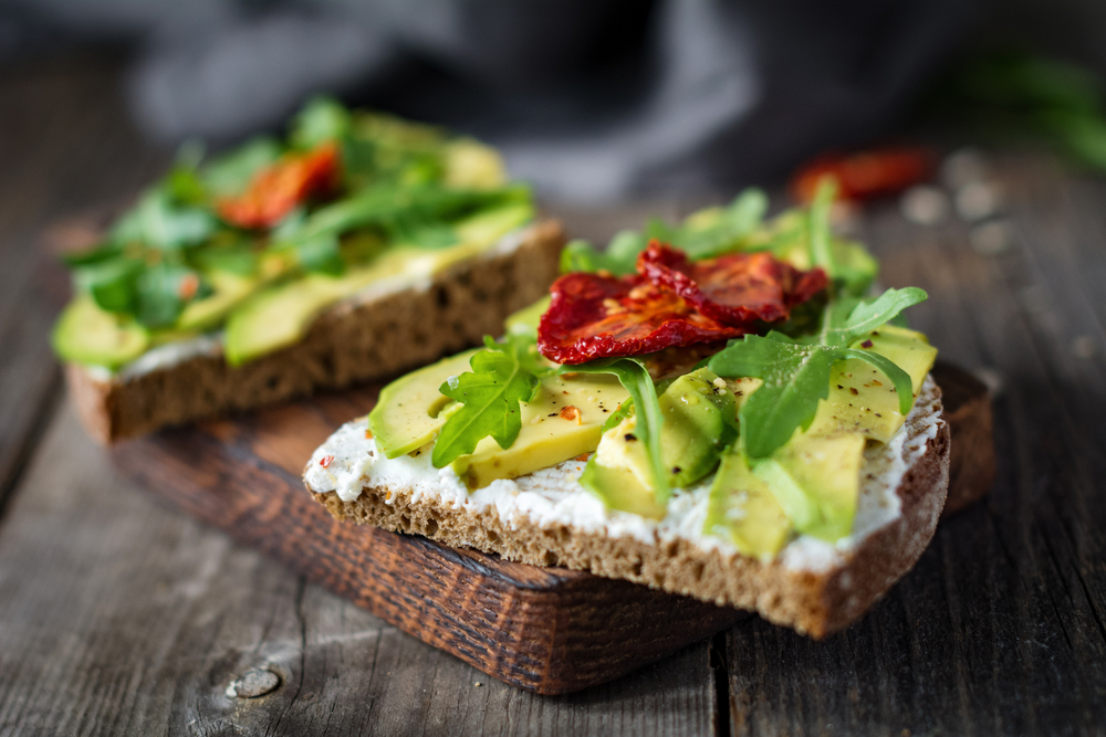 Two pieces of toast with avocado and tomato on in an article about breakfast in Chicago