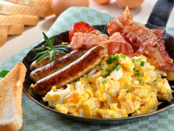 scrambles eggs with fried bacon and sausage in an article about breakfast in Chicago