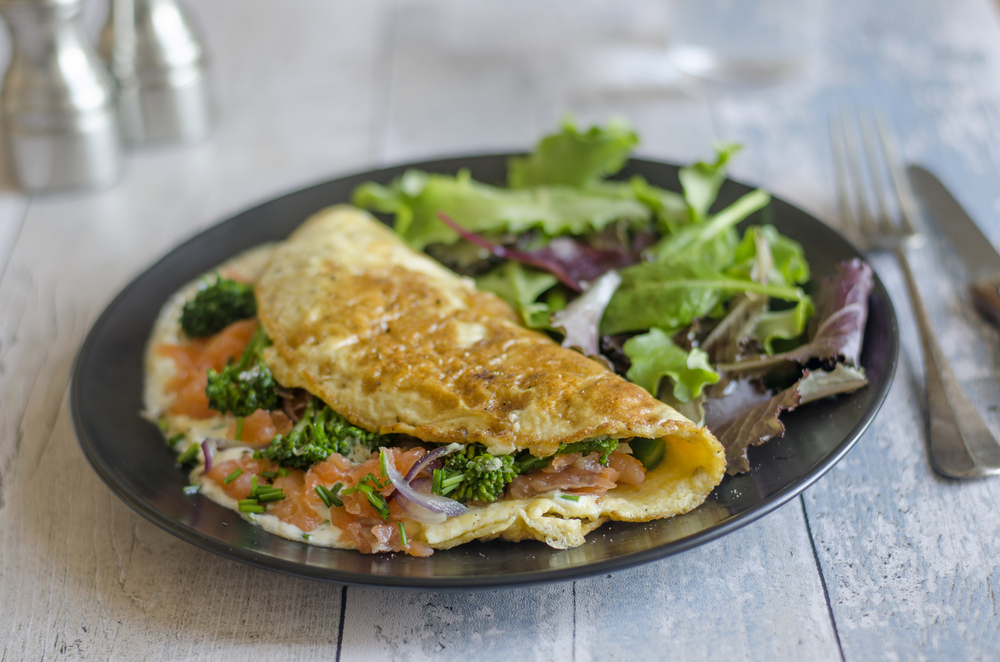 A plate containing salad and a salmon omelet