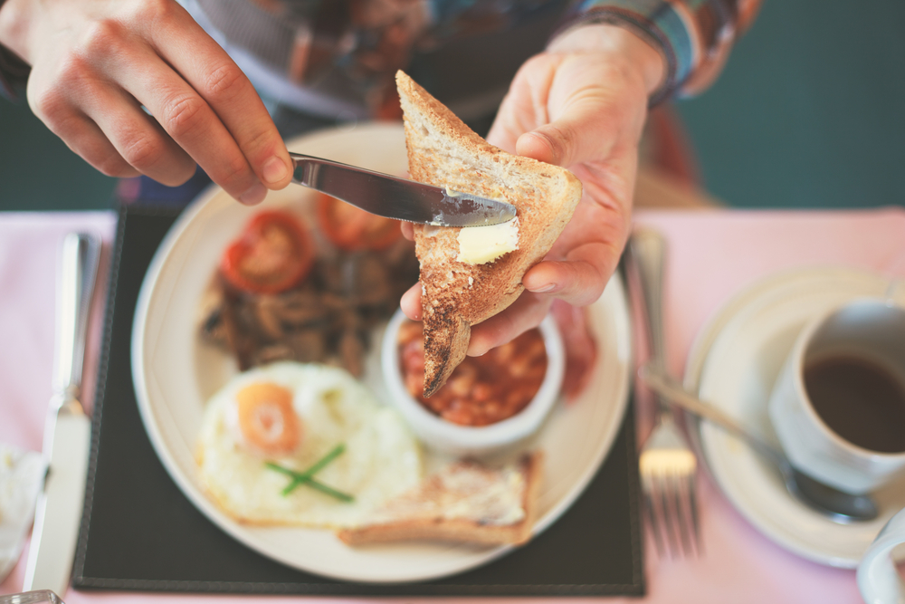 A person buttering toast with a cooked breakfast out of focus