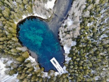 An aerial view of Kitch-iti-kipi, a large freshwater spring that is one of the best things to do in the UP. It is a crystal clear spring with a dock on it. It is surrounded by trees and snow on the ground.