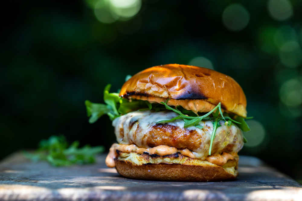A charizo burger with a creamy orange sauce, cheese, and spinach. The bun is toasted. The burger is sitting on a dark material and there is a green and black bokeh background.