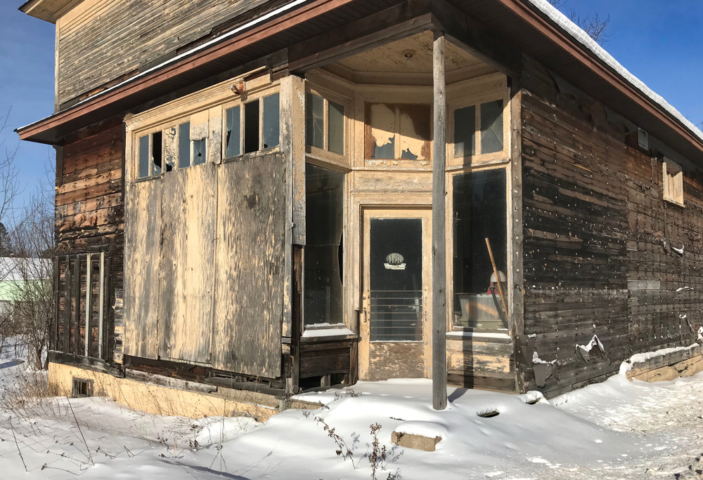 An abandoned building in a mining town in Michigan. It looks like it was once a store front. It is badly decaying with wooden sides that looks like they have mold and mildew on them. One side of the windows are boarded up, but the top  windows are broken. There are two large windows and a glass door in that make a corner in the front of the building. Those windows are still mostly intact. The old trim on the windows and doors is a faded and dirty yellow. There is snow on the ground in front of the dilapidated building.