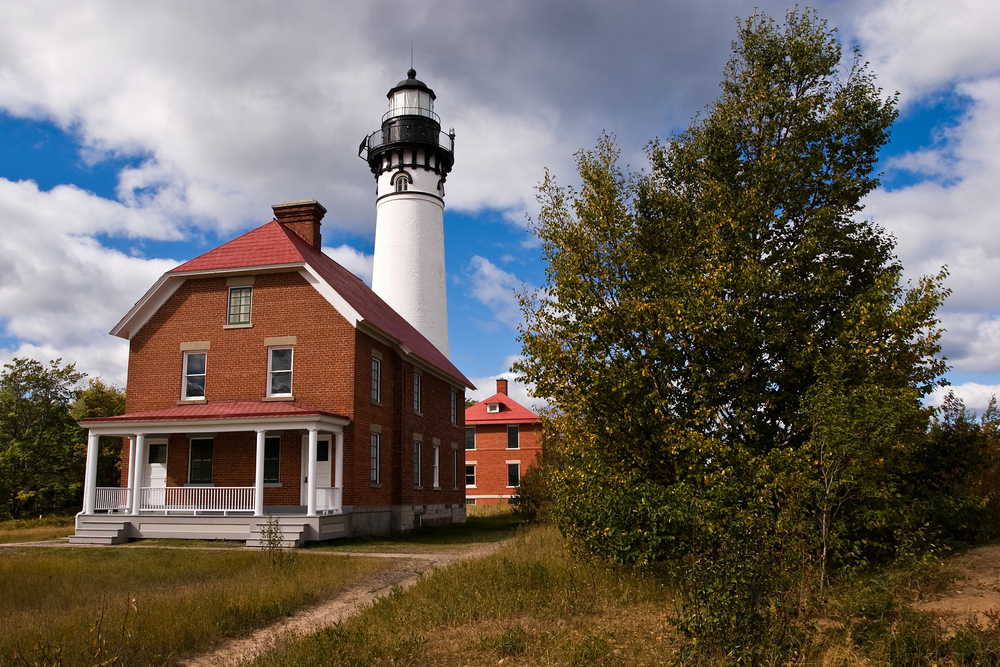 The Au Sable Light station. It is a brick building with a small white lighthouse behind it. The house has a red roof, a small front porch, and white trim. There is another smaller brick building behind it. In front there is grass and trees.