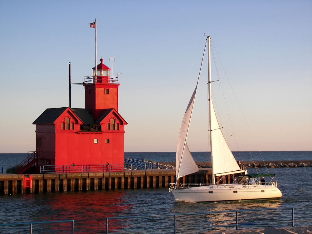 A large red lighthouse on a dock that looks like it has architectural designs inspired by Holland. In front of the lighthouse is a large sailing boat with big white sails. The sun is setting on the lake.
