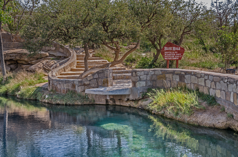 """A crystal blue lake with grass and shrubs around it. There is a stone wall along the side and stone steps that lead down to the lake. There is also a sign that says """"Blue Hole"""" and lists different information about the lake."""