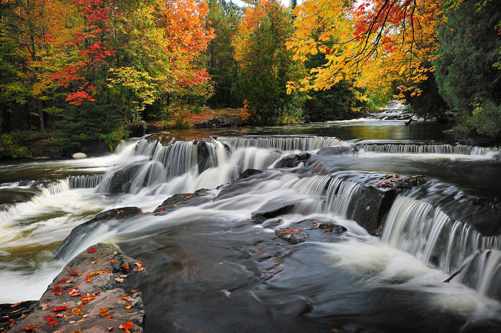 A large waterfall with cascading falls over several large rock formations in the river. You can see the river flowing to the rocks in the background. The river and falls are surrounded by trees with yellow, orange, red, and green leaves. There are some dead leaves on the rocks in the waterfall.