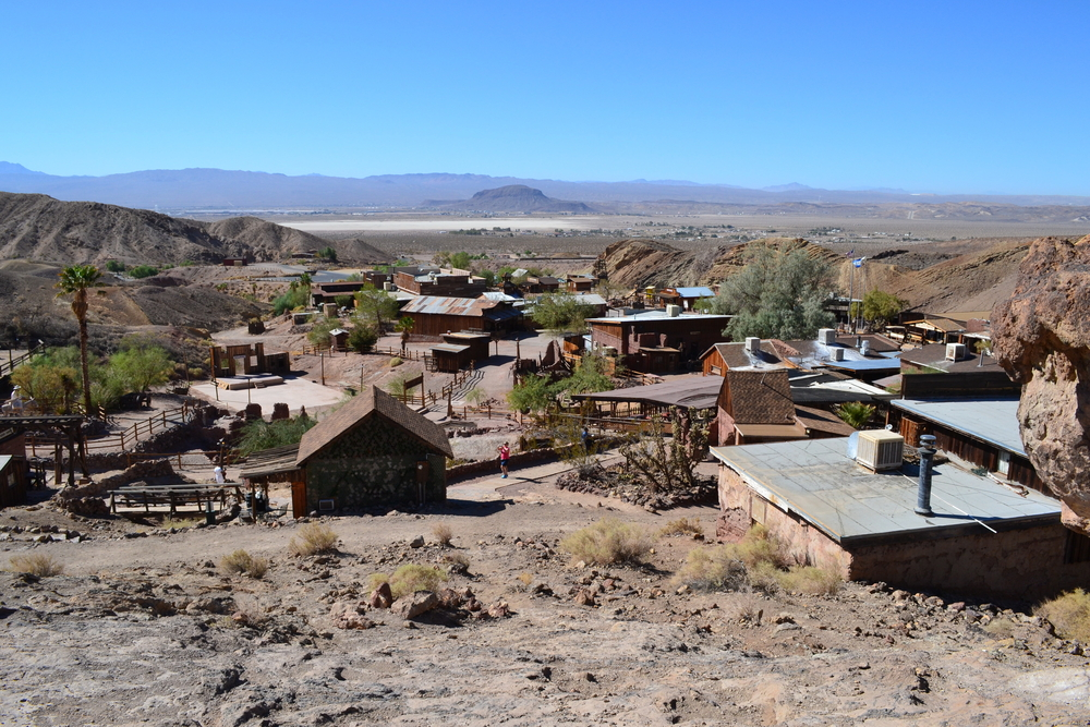 A view of the Calico Ghost Town in the desert of California. There are several old buildings scattered around the desert and walkways to get to them. In the distance you can see some mountains. Route 66 attractions