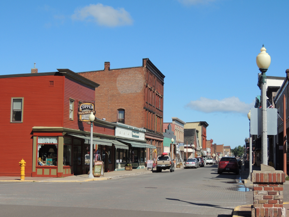 A street view of the historic town of Calumet. There are historic buildings and shops with cars parked on the side of the street.