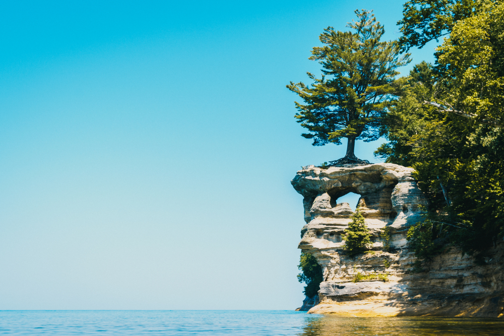 the view from the shore of the lake of Chapel Rock. It is a rock formation that goes into the lake and has a hole in the top center of the side of the rock formation. There is a tree growing directly on top of the rock formation, and trees surrounding it.