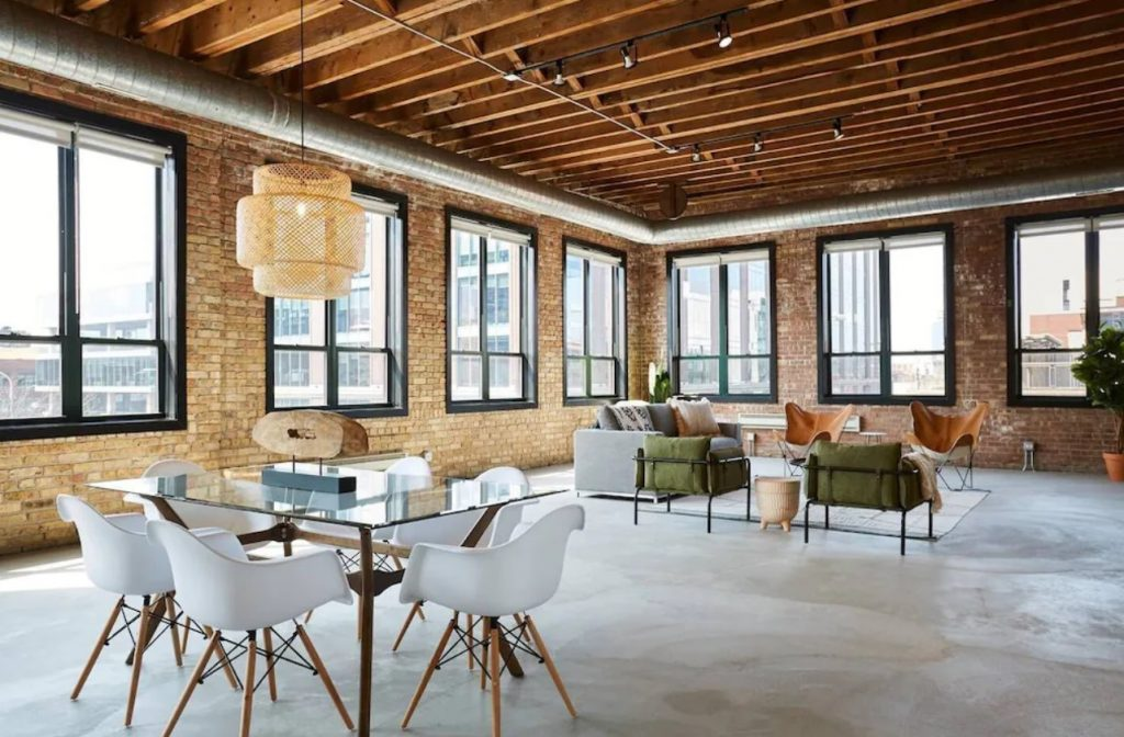 The interior of a loft penthouse in Chicago. There are exposed brick walls, open industrial beam ceilings and lots of windows with black trim. It is decorated with modern decor including a glass dining table and a sitting area with a couch and four chairs. The chairs are olive green and leather.