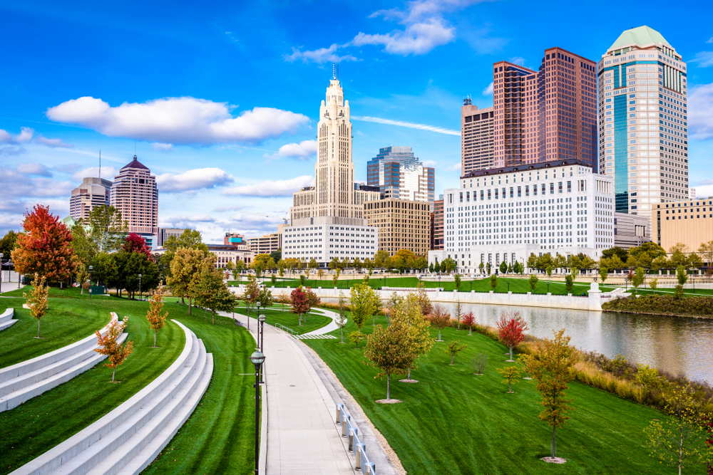 A view of the Columbus Ohio city skyline, a great stop for Ohio road trips. There are several tall buildings that are white, tan, and brick. They are along the river and next to the river is a park with lots of green space and trees. The trees have leaves changing to red and orange.