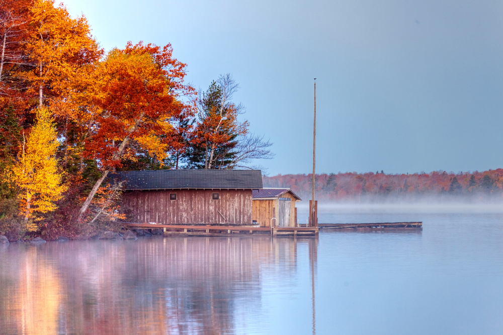An old building and dock on the shores of a lake. It is foggy out and the sky is a muted blue. Behind the old building and dock is a large patch of trees. The trees have yellow, orange, and red leaves. There are one or two trees with dark green leaves.