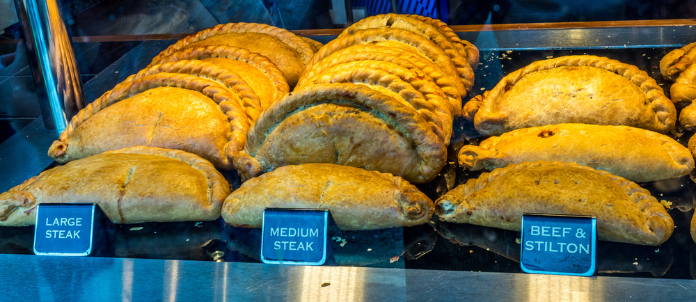 A tray of Cornish Pasties which are a pastry that are folded in half with braided edges and stuffed with meat and vegetables. The pasties are separated by 'large steak' 'medium steak' and 'beef and stilton' flavors.
