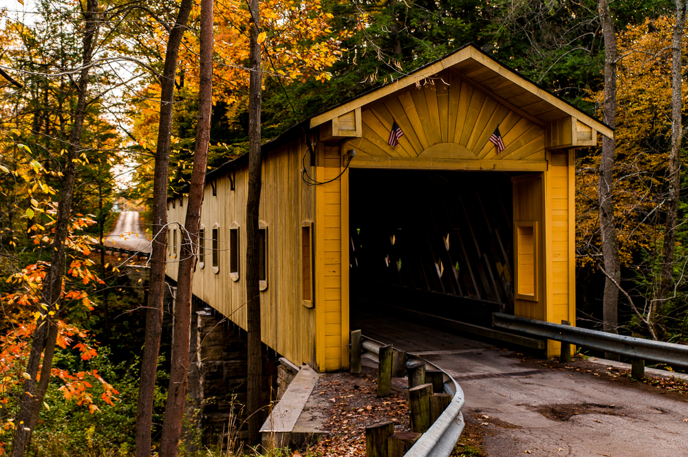 A yellow wooden covered bridge surrounded by fall foliage. There are green trees, but most of the trees are yellow and orange.