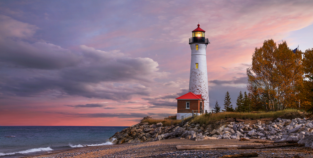 The Crisp Point Lighthouse at the edge of a rocky lake shore. It is a tall white lighthouse with black trim and a red roof. In front of it is a small brick building with a red roof. There are trees with brown leaves near it. It is sunset and the sky is pink and purple