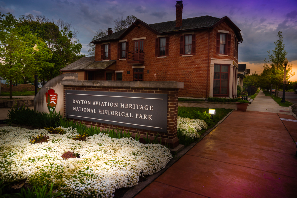 The entrance to the Dayton Aviation Heritage National Historical Park. There is a big brick sign with white flowers in front of it and the National Park Service logo on it. Behind the sign is a brick building that resembles a home.