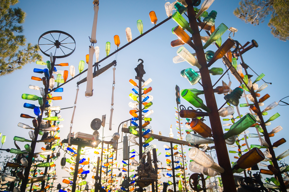 Large metal poles with bottles of all different colors attached to them. The sun shines through them and it is a clear blue sky.