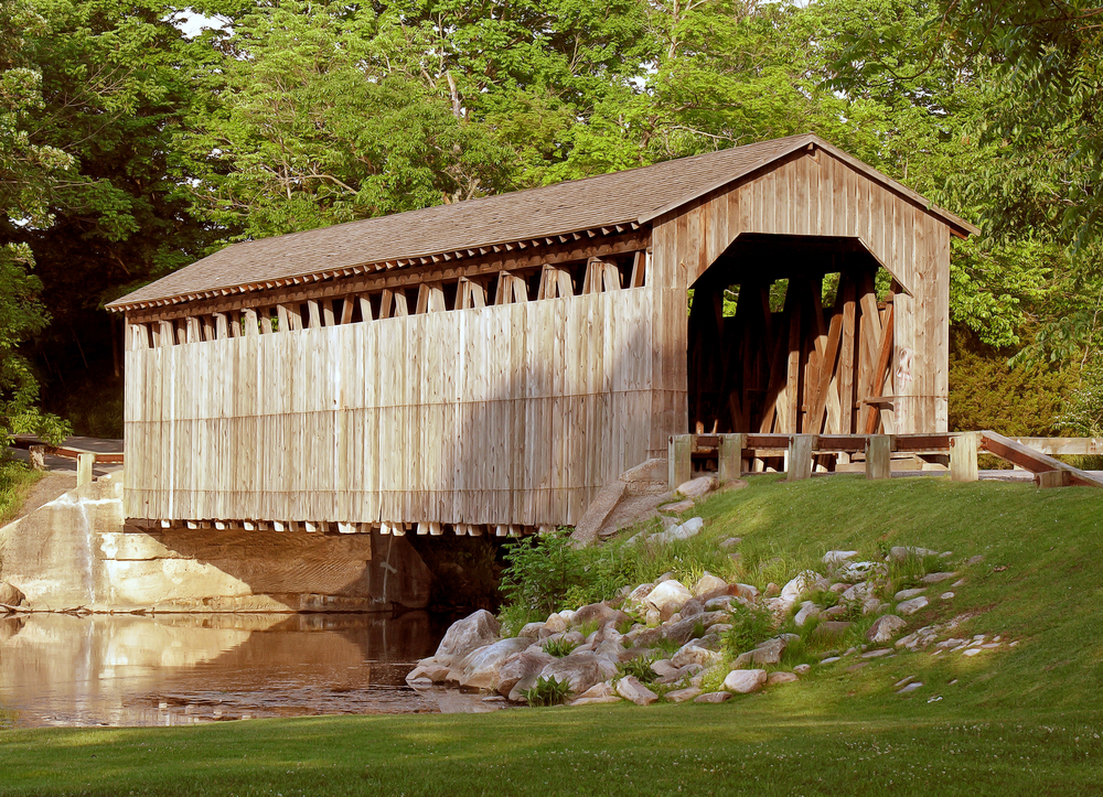 A large wooden covered bridge that crosses a small river. There is a grassy hill next to the road that leads to the bridge and there are rocks along the shore of the small river. The covered bridge is surrounded by trees on the other side, all with green leaves.