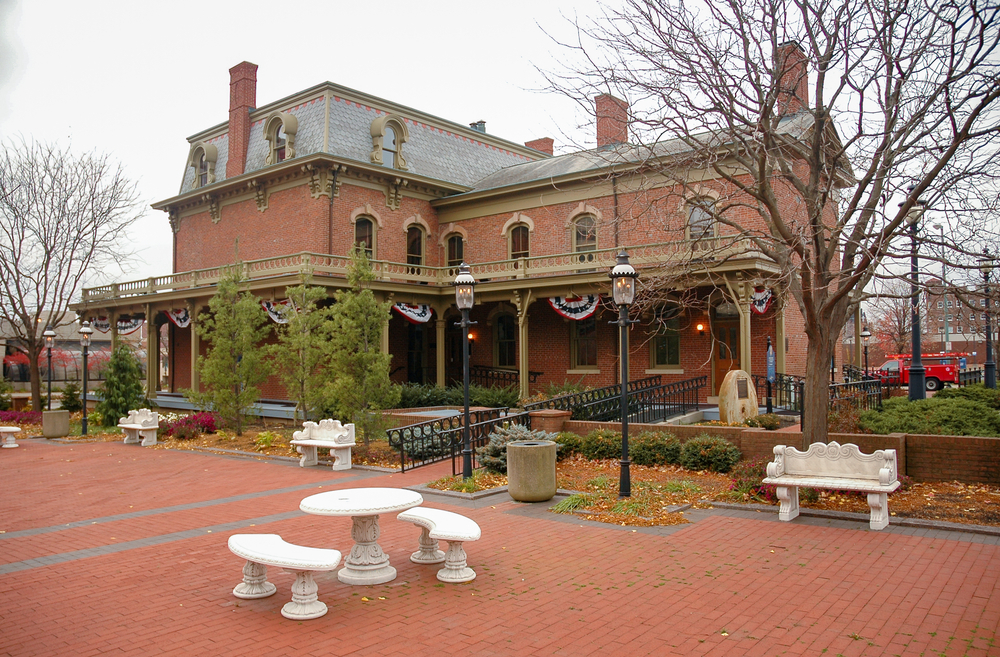 The exterior of the First Ladies Historic Site. It is an old brick building with tan trimmings and multiple chimneys. On the building there are American flag pennants. There is a brick courtyard with white stone benches and tables. Around the building there are trees and shrubs.