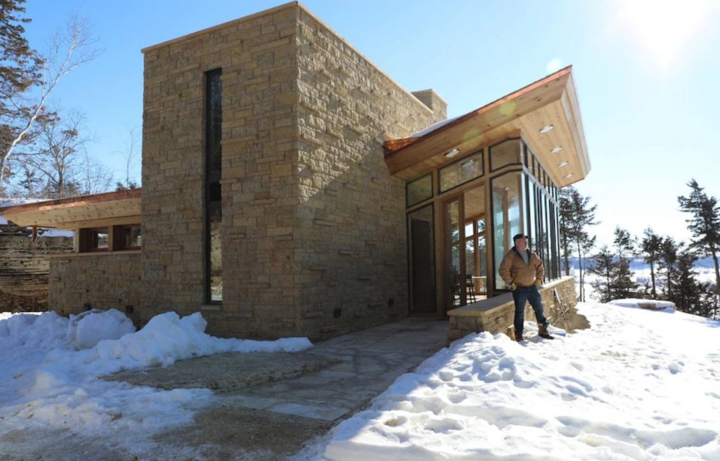 The exterior of a Frank Lloyd Wright inspired cottage on a mountain. The structure is very angular and made of natural stone and wood. To the side there is a large space that is walls of windows. There is snow on the ground and a man standing proudly in front of the cottage.