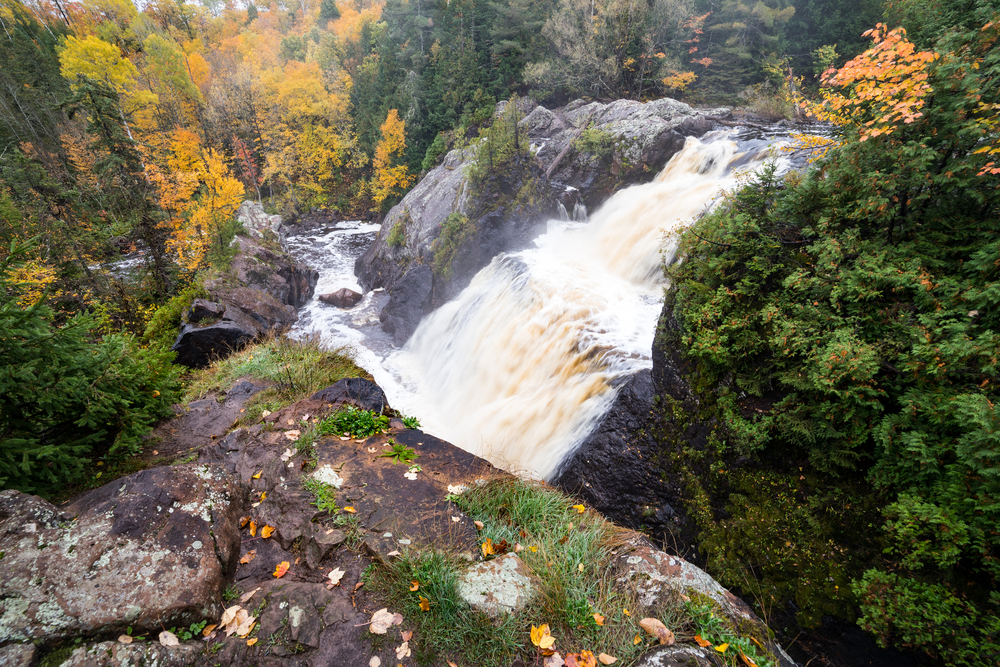 A large rocky formation and waterfall flowing over the rocky formation. Down the river bank you can see lots of tall trees. Most of the trees have yellow and orange leaves. There are some pine trees as well as trees with no leaves. There is moss and grass growing on the rocks.