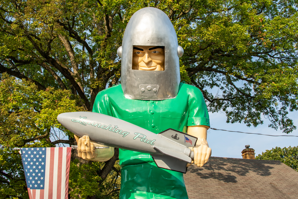 A large vintage metal sculpture that looks like a moon man. He is wearing a green jumpsuit and a silver metal 'moon' helmet. The Gemini Man is holding a grey rocket with the words 'Launching Pad' written in green on it, with an American flag and another decal. He is also holding an American flag. There is the roof of a building and a large green tree in the background