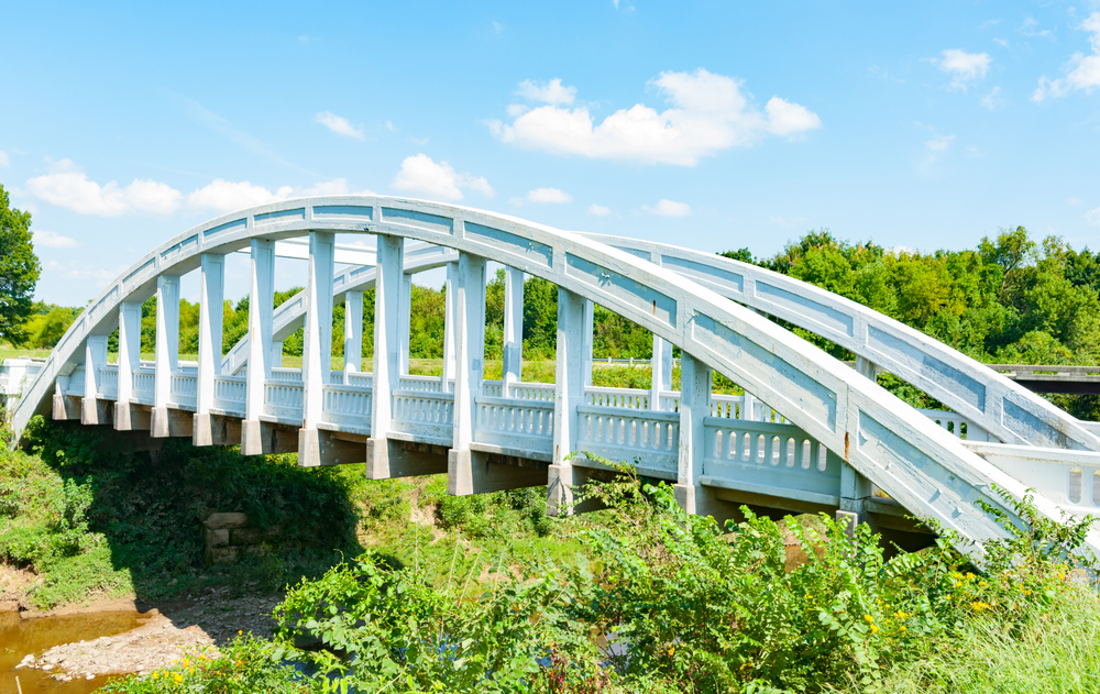 A bluish-white bridge that has an arch shape on both sides of the road. There is a river or stream running underneath it. Around the bridge there is a ton of greenery like shrubs, grasses, and trees