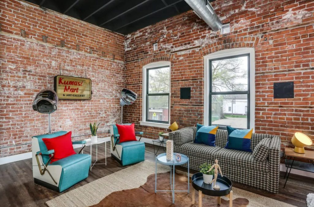 The living area of a loft in Detroit. It has exposed brick walls and an exposed industrial ceiling. It is decorated with vintage furniture like two blue and white barber's chairs, a black and white hounds tooth couch with blue and yellow pillows, and a hemp and cow hide rug. There are two large windows in the room. Its one of the best airbnbs in the Midwest