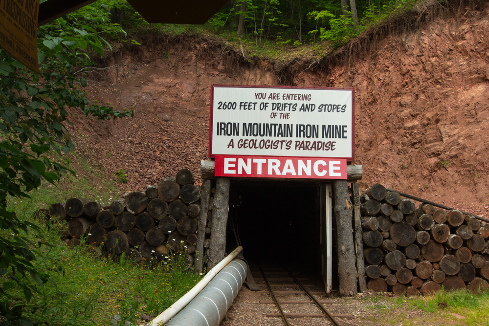 The entrance to the Iron Mountain Iron Mine. It is a dark tunnel with wood blocks around it and a large white sign that says 'you are entering 2600 feet of drifts and stopes of the iron mountain iron min a geologist's paradise' with a red Entrance sign under that. The tunnel is in the side of a rocky hill with grass in front of it. Its one of the best things to do in the UP.