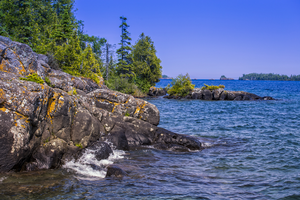 The shore of Isle Royale National Park. It is a rocky shoreline with moss growing on the rocks. There are trees growing on the rocky shore and there are small waves in the lake. In the distance you can see another land mass. Its one of the best things to do in the UP.
