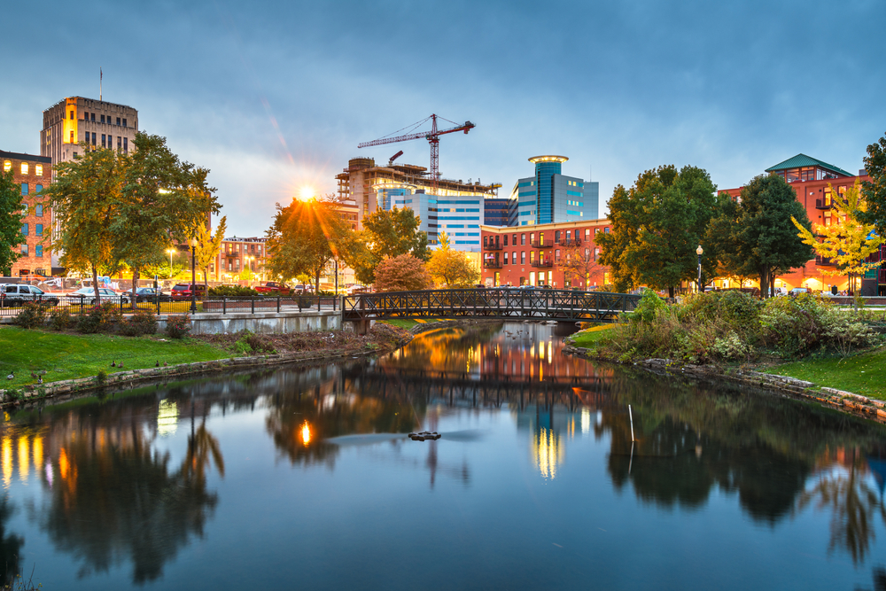 The city skyline of Kalamazoo Michigan, a large city. It is twilight, so the city is all lit up and the sun is setting. The main part of the picture is a large pond in the middle of the city with a metal bridge going across it with the skyline behind it. Its a great stop for Michigan road trips
