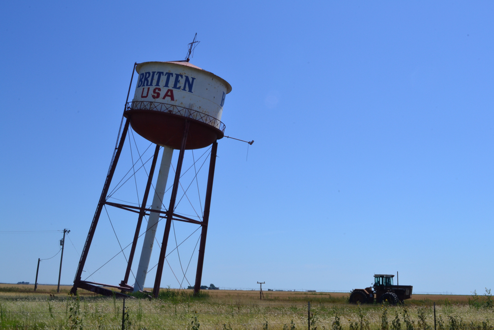 A white water tower leaning over at a serious angle over a field. In the field, a tractor is parked near the leaning tower and there is grass growing.