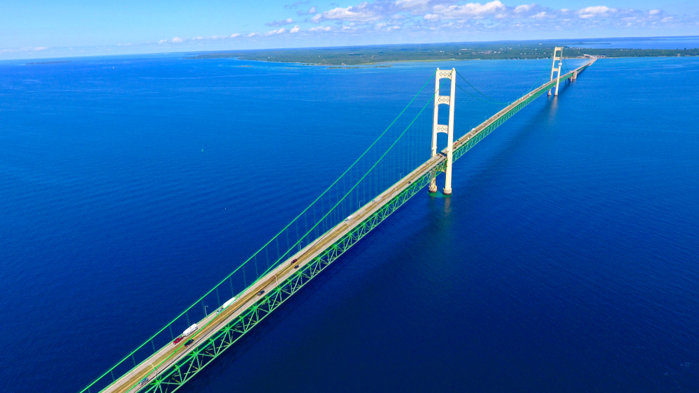 An aerial view of the Mackinac Bridge over the peaceful lake water. The bridge is similar in style to the golden gate bridge but it is painted white and green. It leads in this photo to Mackinac Island.