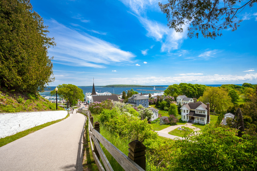 The view from a walking trail of Mackinac Island. You can see historic homes, a church steeple, and the lake. There are a ton of trees and tall grasses near the walking trail and throughout the view of the island. Mackinac Island are great things to do in the UP